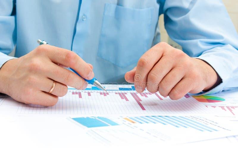 指向商业文件的男性手的图象在讨论时在会议上 图库摄影