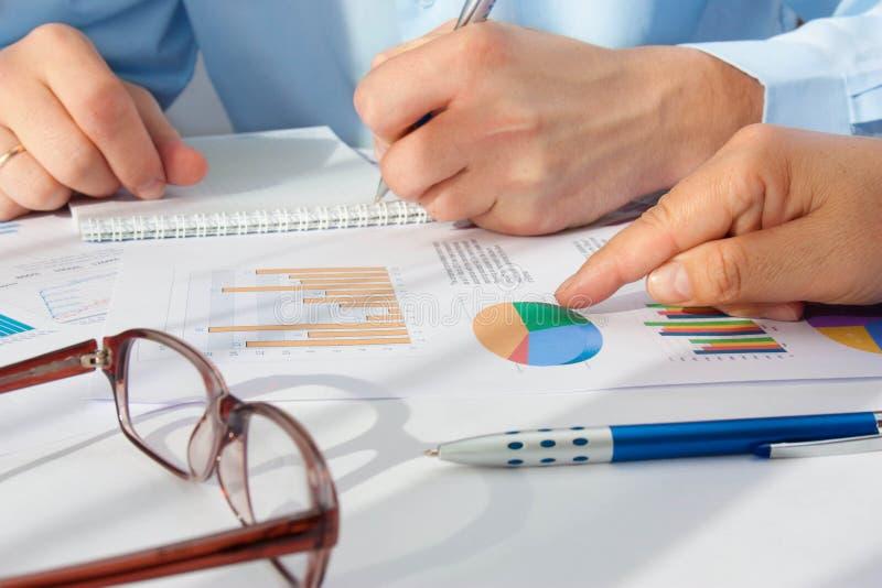 指向商业文件的男性手的图象在讨论时在会议上 免版税图库摄影