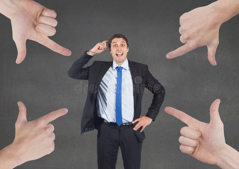 指向商人的手反对灰色背景 免版税图库摄影