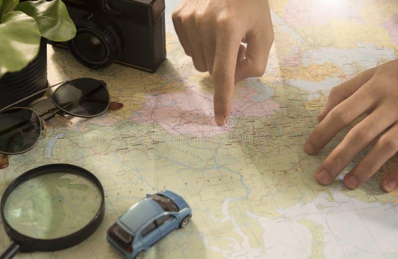 指向在世界地图的游人为计划的假期 库存图片