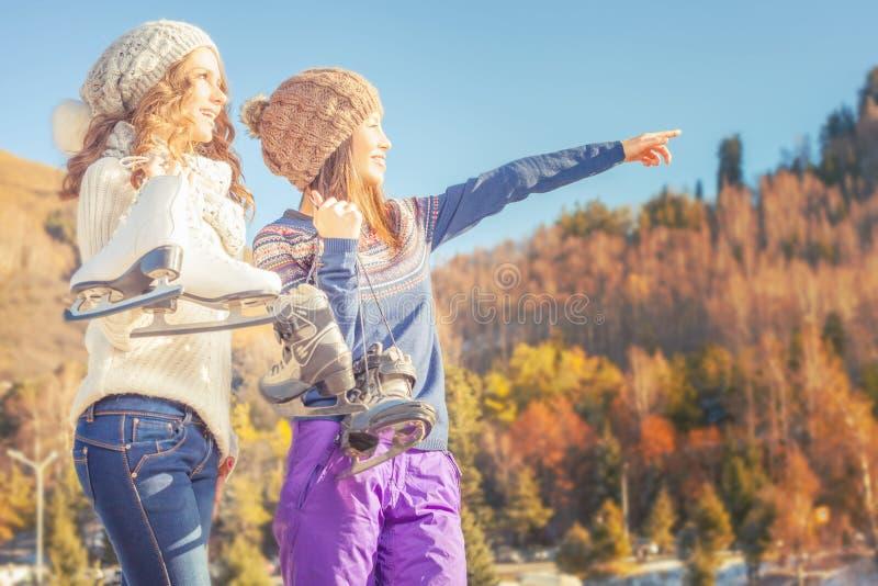 指向在冰鞋溜冰场的愉快的多种族妇女 免版税库存图片