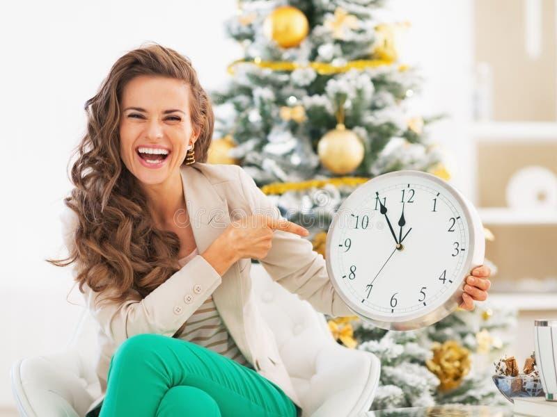 指向在圣诞树前面的时钟的愉快的少妇 库存图片
