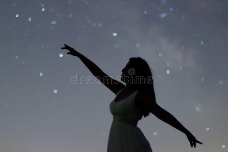 指向在夜空的跳舞妇女的剪影 妇女剪影在繁星之夜下, Defocused银河星系 库存图片