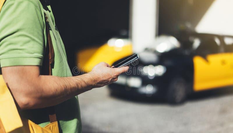 指向在屏幕智能手机的人手指在背景黄色出租汽车,使用在手手机,人的旅游行家连接 免版税库存照片