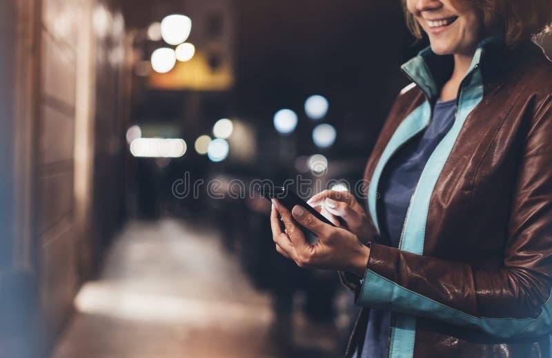 指向在屏幕智能手机的女孩微笑手指在背景照明颜色光在夜大气城市,行家使用 免版税库存照片