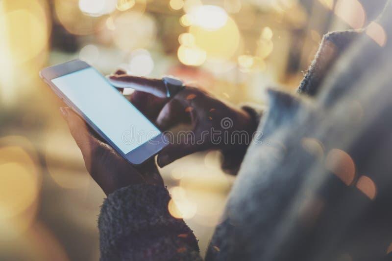 指向在屏幕智能手机的女孩手指在夜大气城市 发短信给消息手机的女性手 特写镜头 库存照片
