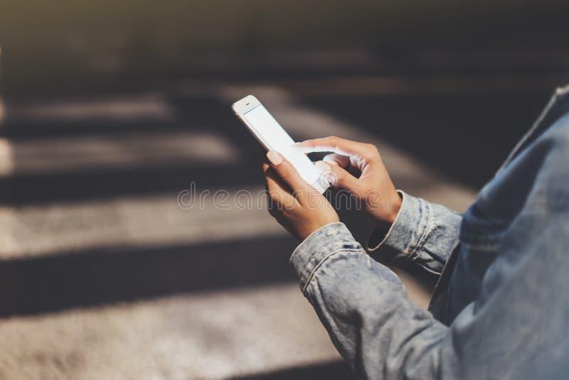 指向在屏幕智能手机的女孩手指在背景焕发bokeh光在夜大气圣诞节城市,行家使用 免版税库存照片