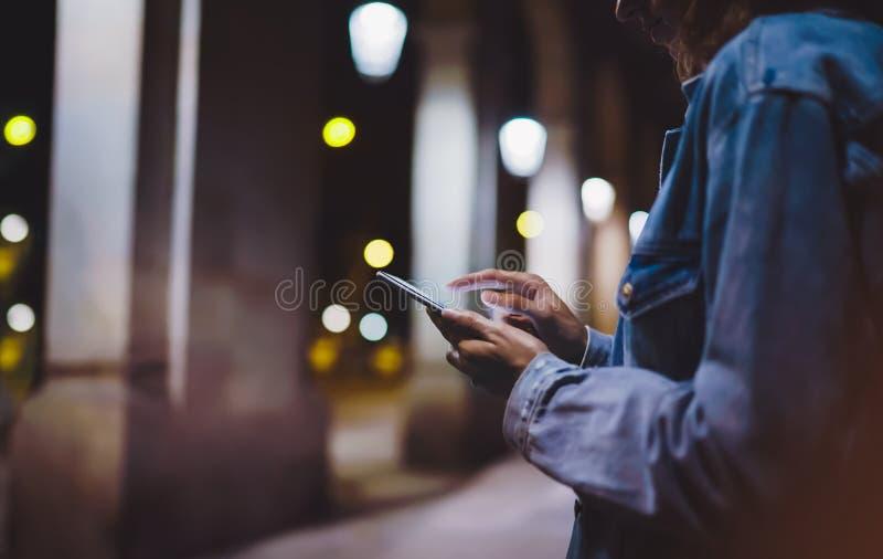 指向在屏幕智能手机的女孩手指在背景照明焕发bokeh光在夜大气城市,行家使用 免版税图库摄影