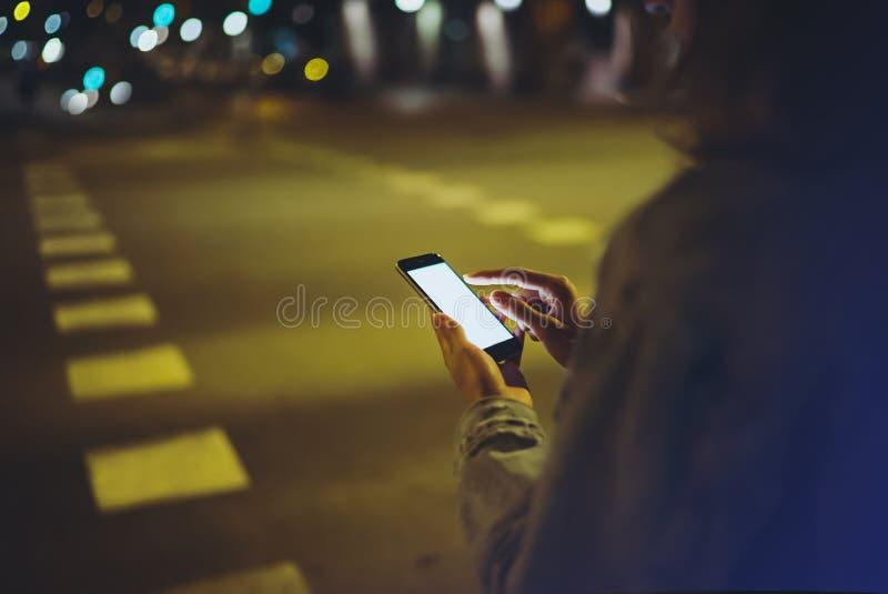 指向在屏幕智能手机的女孩手指在背景照明焕发bokeh光在夜大气城市,行家使用 库存图片