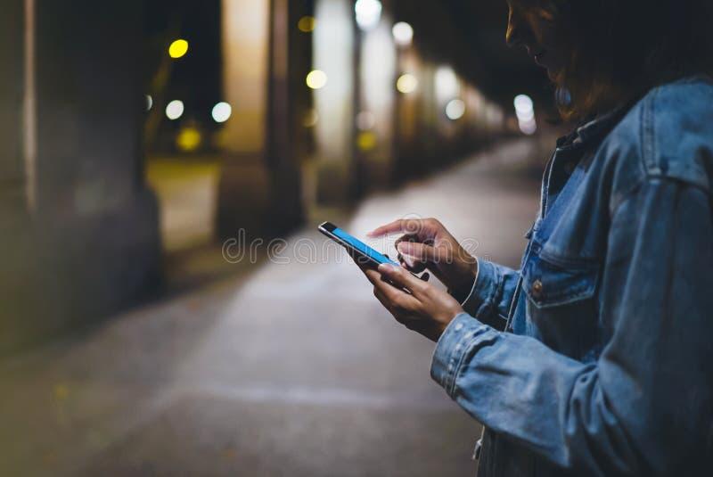 指向在屏幕智能手机的女孩手指在背景照明焕发bokeh光在夜大气城市,行家使用 免版税库存图片