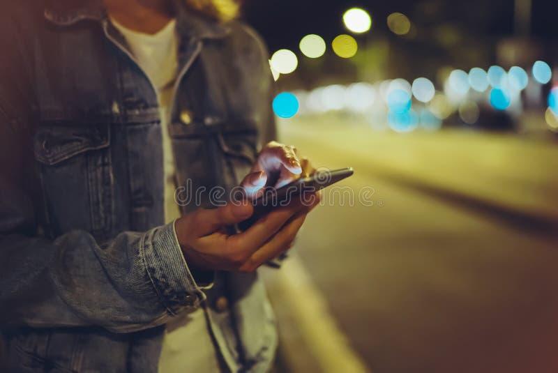 指向在屏幕智能手机的女孩手指在背景照明焕发bokeh光在夜大气城市 图库摄影