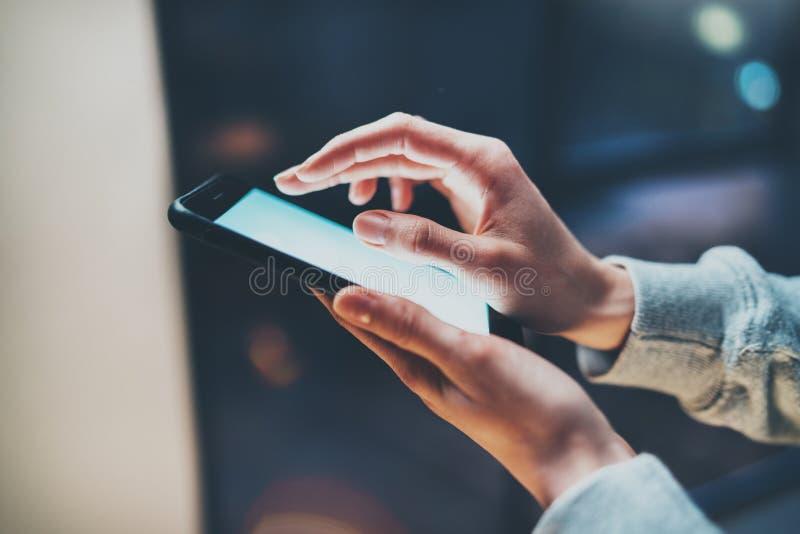 指向在屏幕智能手机的女孩手指在背景照明焕发bokeh光在大气的夜 水平 库存照片
