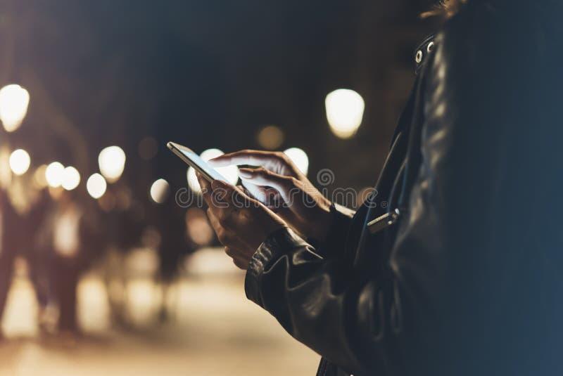 指向在屏幕智能手机的女孩手指在背景照明颜色光在夜大气城市,行家使用 免版税库存图片
