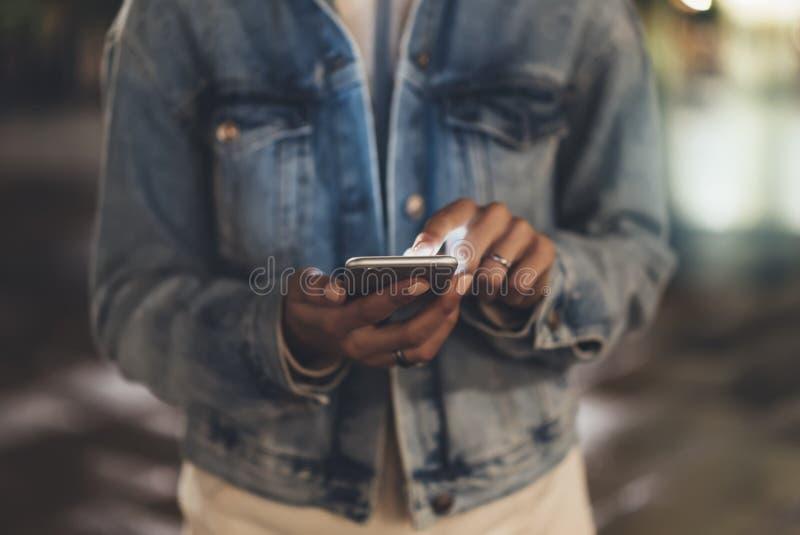 指向在屏幕智能手机的女孩手指在背景照明bokeh光在夜大气城市,使用在femal的行家 免版税图库摄影