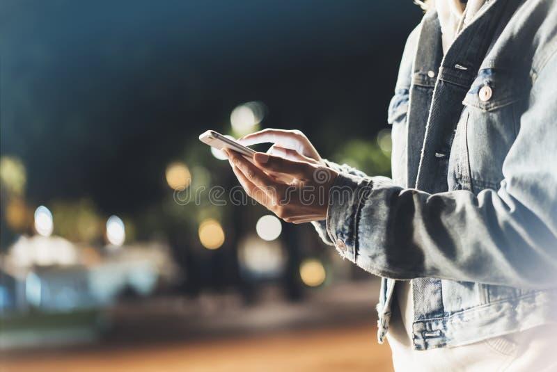 指向在屏幕智能手机的女孩手指在背景照明bokeh颜色光在夜大气城市,使用的行家  免版税库存图片