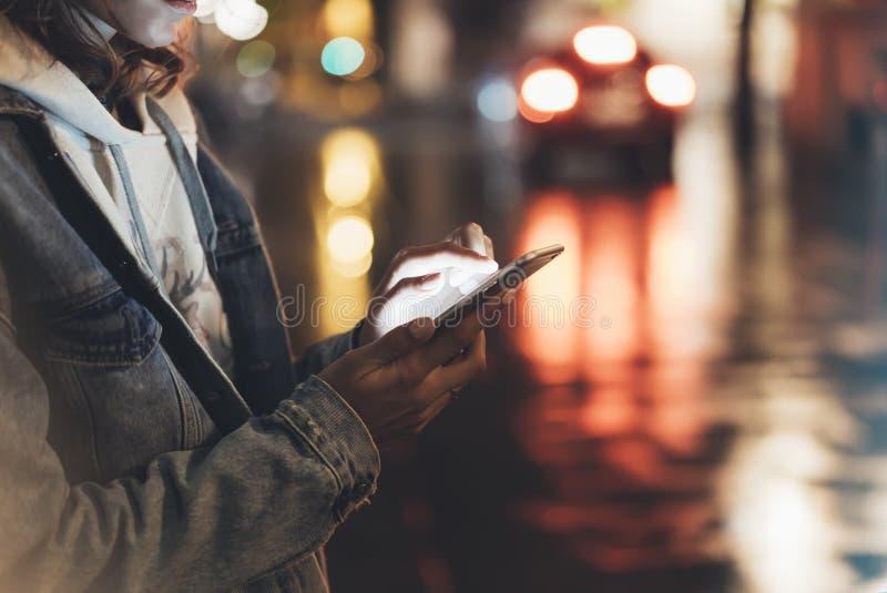 指向在屏幕智能手机的女孩手指在背景照明bokeh颜色光在夜大气城市,使用的行家  图库摄影