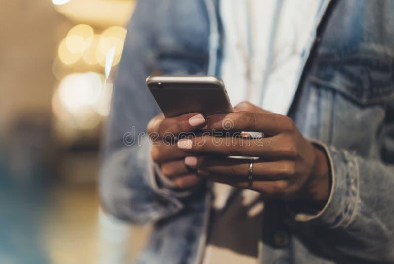 指向在屏幕智能手机的女孩手指在背景照明bokeh颜色光在夜大气城市, 免版税库存照片