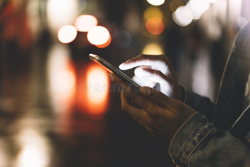指向在屏幕智能手机的女孩手指在背景照明bokeh颜色光在夜大气城市 库存照片