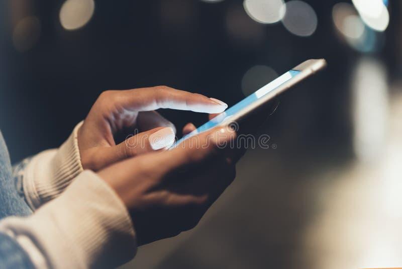 指向在屏幕智能手机的女孩手指在背景照明bokeh颜色光在夜大气城市 免版税图库摄影
