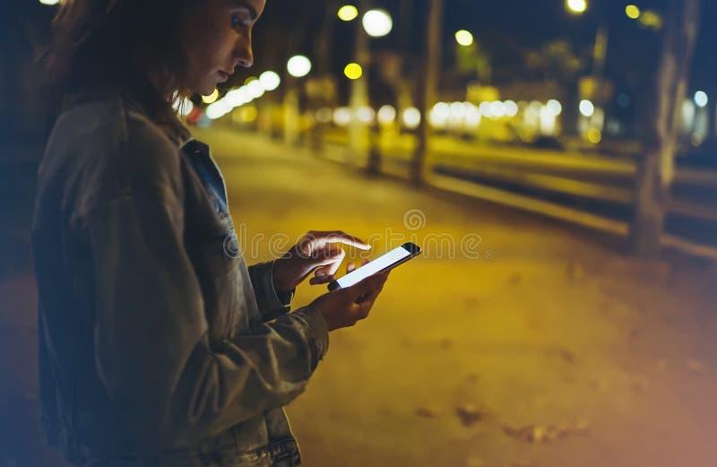 指向在屏幕智能手机的妇女手指在背景照明bokeh光在夜大气城市,在手中使用的行家 库存图片