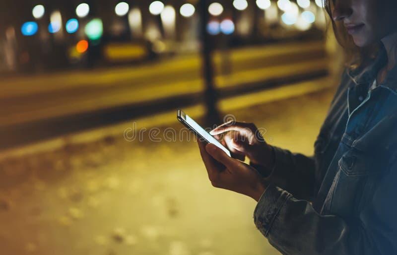 指向在屏幕智能手机的妇女手指在背景照明bokeh光在夜大气城市,在手中使用的行家 免版税图库摄影
