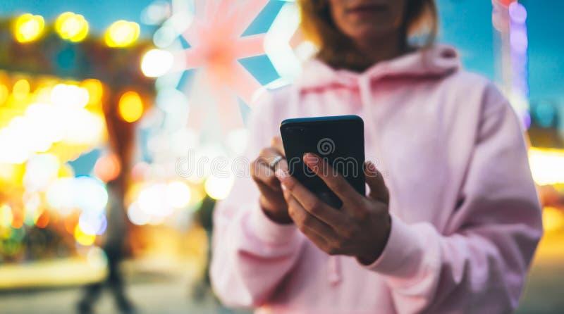 指向在屏幕智能手机的正面图女孩手指在defocus背景在晚上街道吸引力,使用i的妇女的bokeh光 免版税库存照片