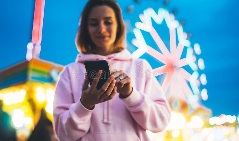 指向在屏幕智能手机的正面图女孩手指在defocus背景在晚上街道吸引力,妇女使用的bokeh光 免版税库存图片