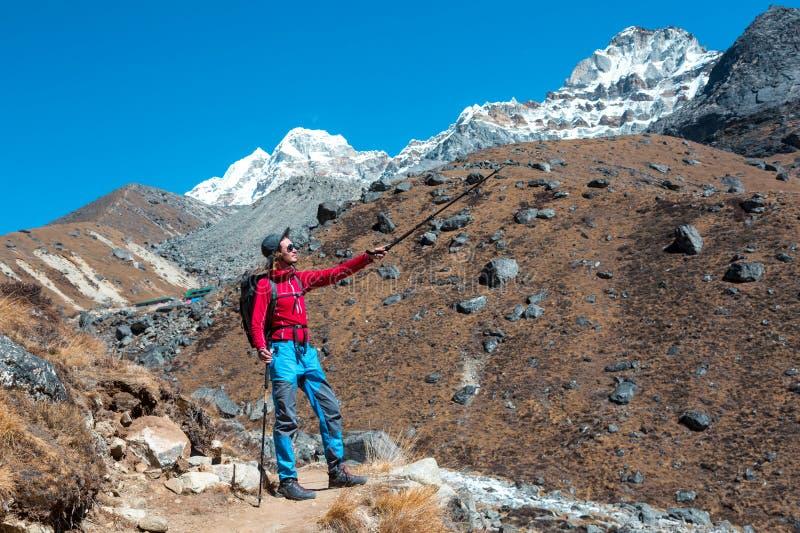 指向在山山顶的年轻男性远足者用拐棍 库存照片