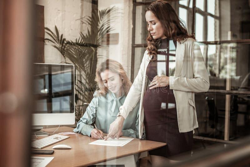 指向在必要的信息的刚毅怀孕的经理 免版税库存图片