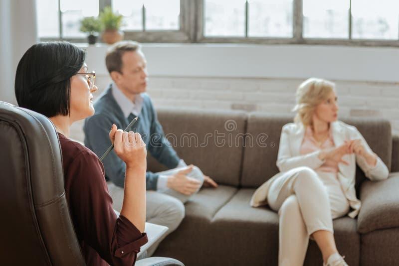 指向在必要的信息的被集中的短发女性心理治疗家 免版税库存图片