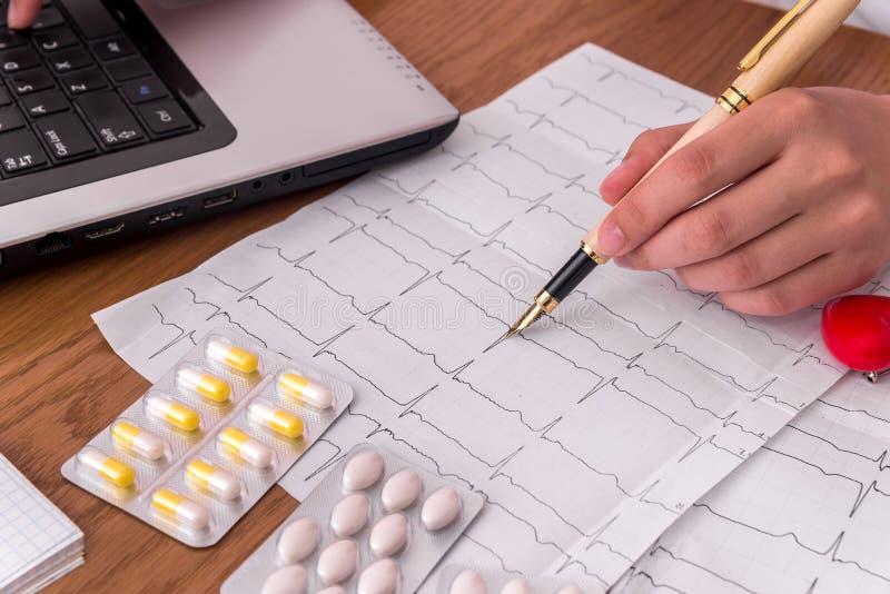 指向在患者的心电图、药片和红心的医生 免版税库存照片
