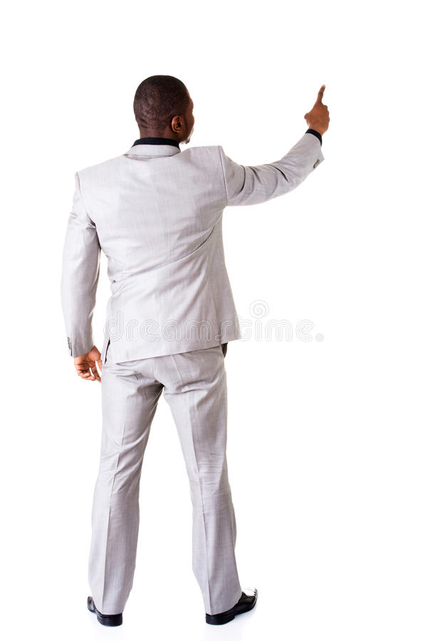 指向在拷贝空间的年轻商人。后面看法。 免版税库存照片