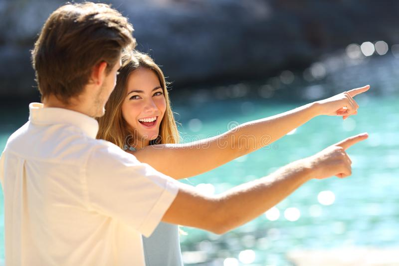 指向在海滩的结合青少年在度假 免版税库存照片