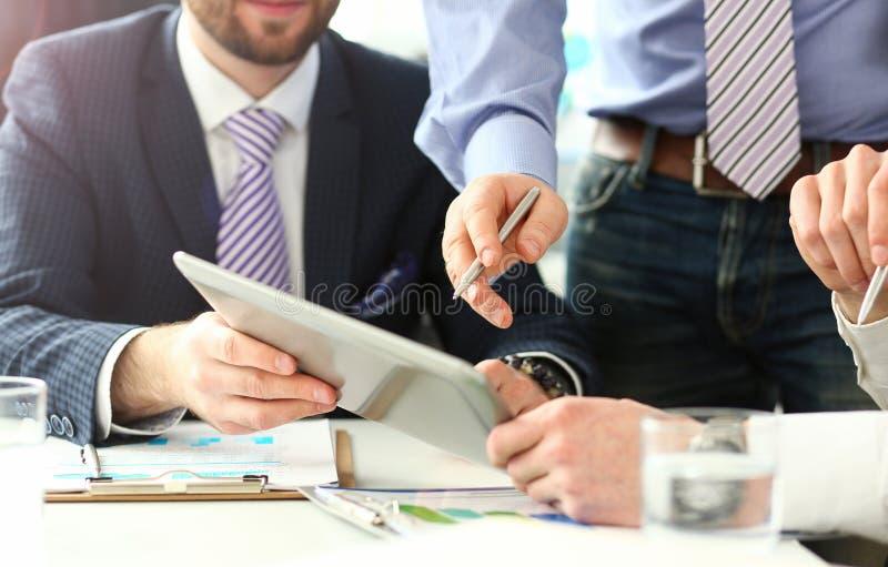 指向在片剂计算机的男性手在与顾客和客户的业务会议期间 库存图片