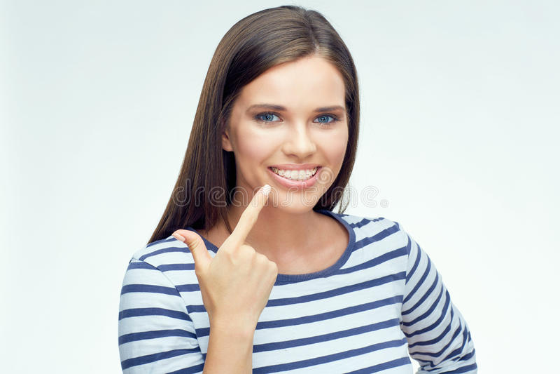 指向在牙齿括号的微笑的女孩手指 库存照片