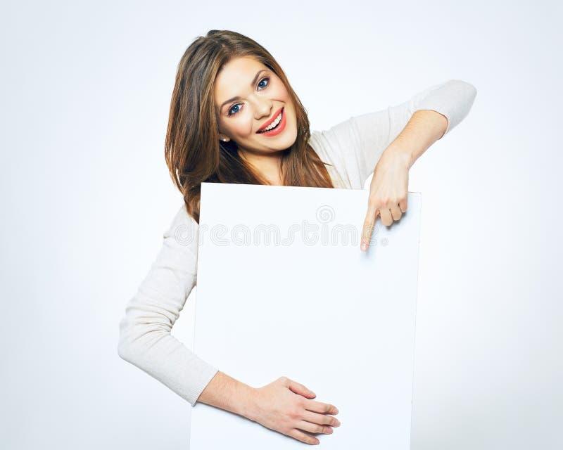 指向在白色空白的名片的微笑的妇女手指 库存照片