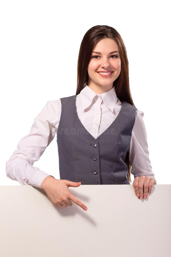 指向在空白的委员会的年轻微笑的妇女 免版税库存照片