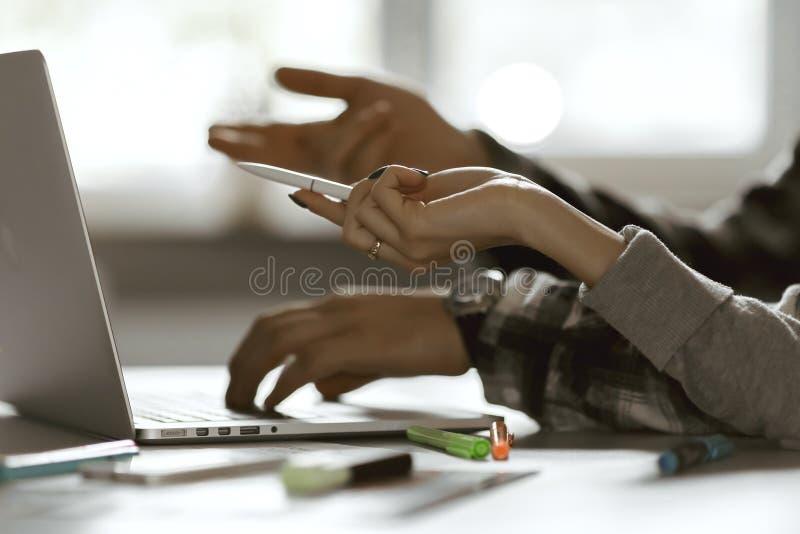 指向在计算机上的男人和妇女的手 库存照片