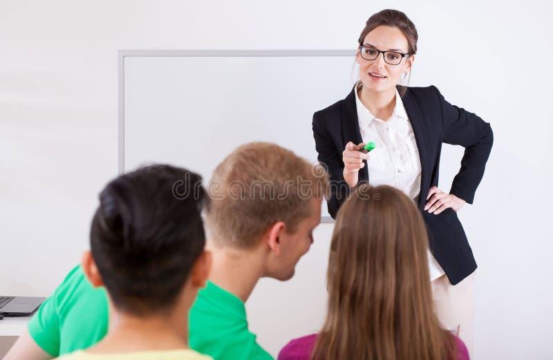 指向在谈的学生的年轻老师 免版税库存图片