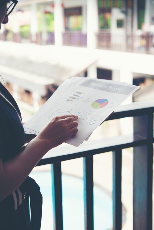 指向在财务图笔记的财政妇女的手,当w时 免版税库存图片