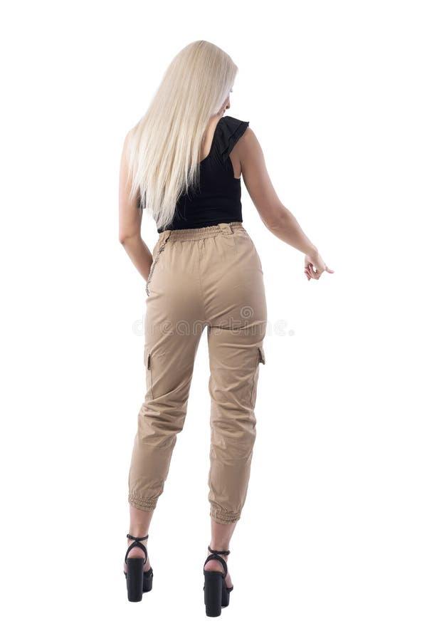 指向在选择或选择的后面观点的时髦的年轻白肤金发的秀丽妇女某事下的手指 库存照片