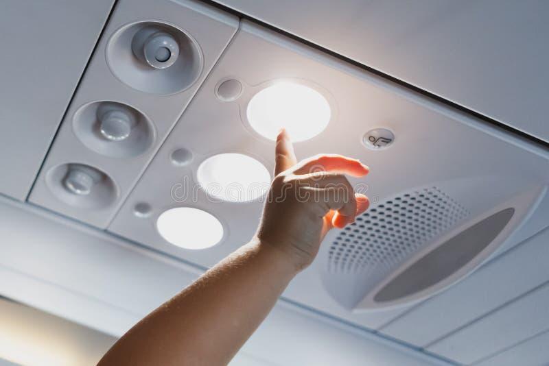 指向在飞机客舱的轻的灯的儿童手 免版税图库摄影