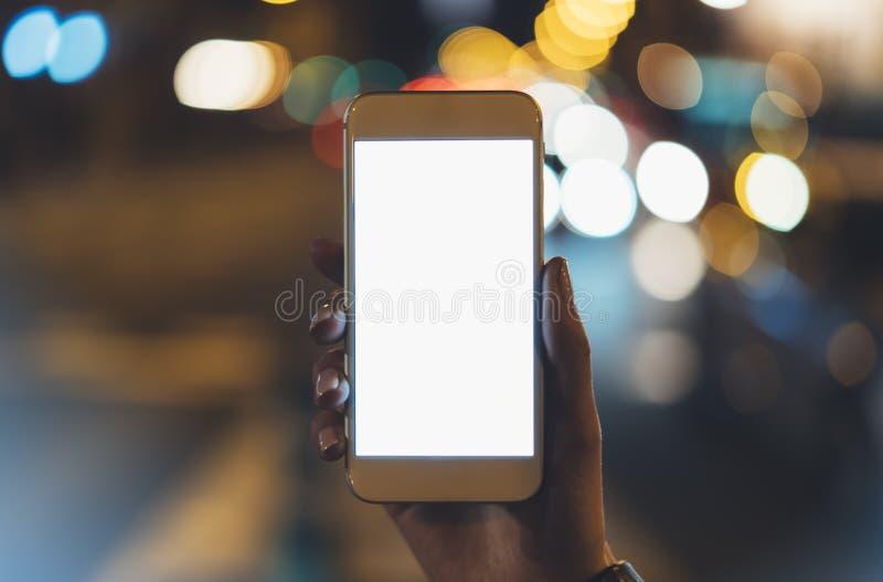 指向在黑屏智能手机的女孩手指在背景照明焕发bokeh光在夜大气圣诞节城市, h 免版税库存照片