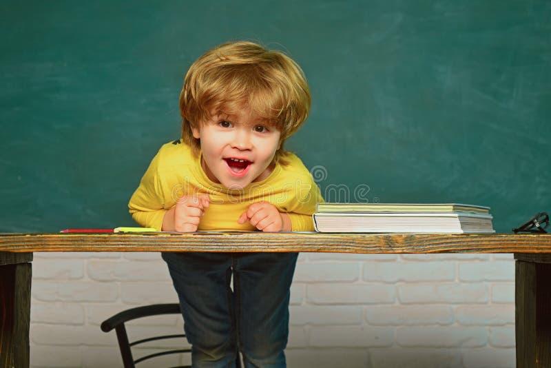 指向在黑板的滑稽的小男孩 r 黑板背景-拷贝空间 在家学会 库存图片