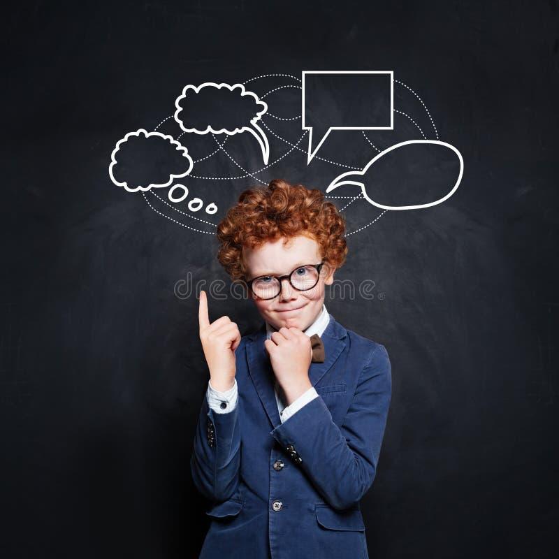 指向在黑板背景的空的讲话云彩泡影的聪明的男小学生 库存图片