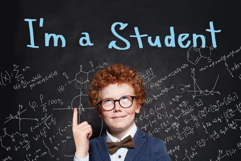 指向在黑板背景的聪明的学生男孩手指与我是学生文本 r 库存照片