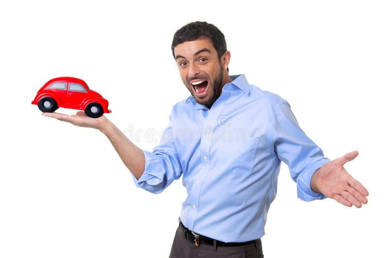 指向在他的手上的年轻愉快的可爱的人大红色玩具汽车 免版税库存照片