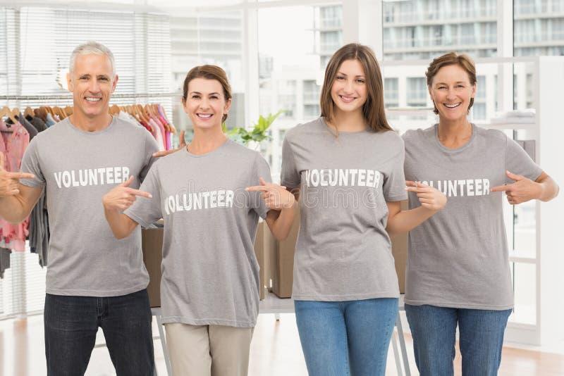 指向在他们的衬衣的微笑的志愿者 免版税库存照片