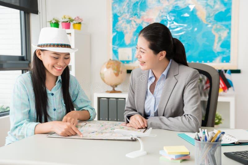 指向地图的女性旅客问旅行问题 库存图片