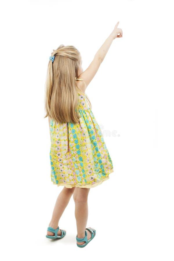 指向墙壁的后面观点的可爱的小女孩 查出的背面图白色 库存照片